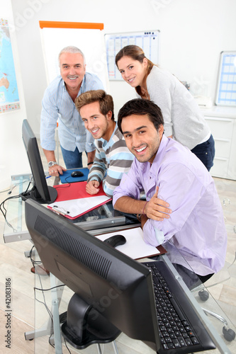 Four people gathered round a computer in a classroom