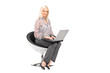 A blond woman sitting on a chair and working on a laptop
