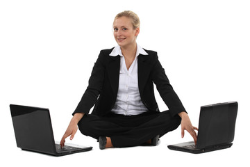 Woman sitting cross-legged in front of two computers