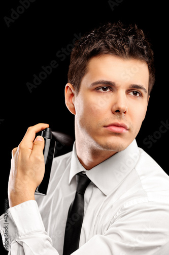 A portrait of a handsome model using perfume
