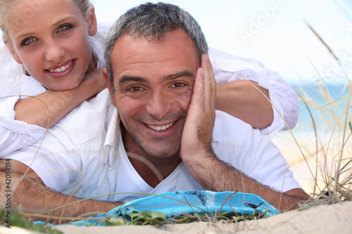 Couple laid on towel at the beach