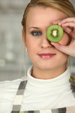 Woman stood with slice of kiwi covering eye