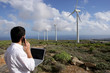 Man with a laptop at a windfarm