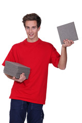 Man with stack of tiles