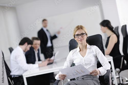 business woman with her staff in background