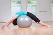 junge frau liegt mit dem Rücken auf gymnastikball