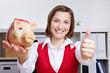 Geschäftsfrau mit Sparschwein hält Daumen hoch