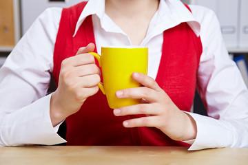 Hände halten Kaffeetasse