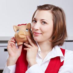 Erfolgreiche Frau mit Sparschwein auf Schulter