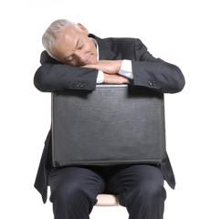 Señor ejecutivo sentado sosteniendo un maletín.