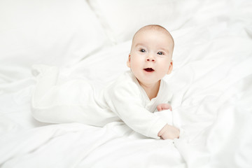 Happy active baby lying on stomach over white bed.  Three month