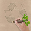 Male hand drawing recycle symbol on Brown Recycled Paper.