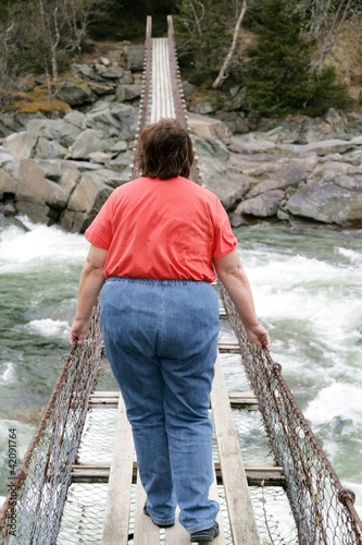 Obese woman on suspension bridge
