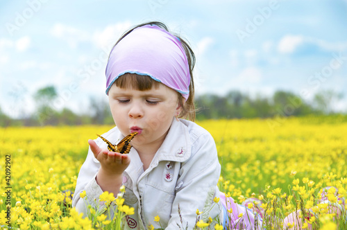 Little cute girl in a field of beautiful yellow flowers.