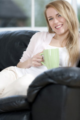 Woman enjoying drink on sofa