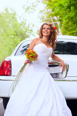 Bride with original bouquet leaning on a white car