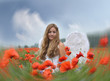 Christmas: Angel on vacation in a field of red poppies