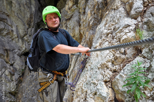 Young man climbing on via ferrata