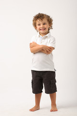 litle boy standing with his arms crossed
