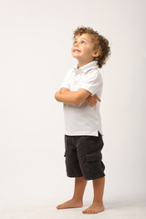 litle boy standing with his arms crossed looking up
