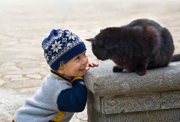 Kind spielt mit schwarzer Katze