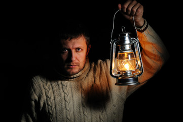 Man in the night with a burning kerosene lamp on black