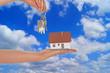Hand mit Eigenheim über blauem Himmel