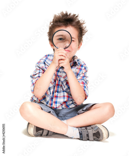 Attentive little boy with weird hair researching using magnifier