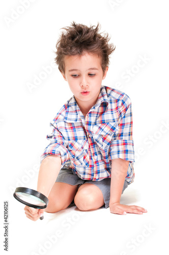 Little boy with weird hair researching using magnifier