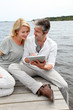 Couple sitting on boardwalk and using tablet