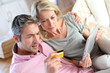 Couple sitting in sofa with electronic tablet