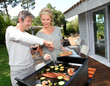Couple in garden cooking meat on barbecue