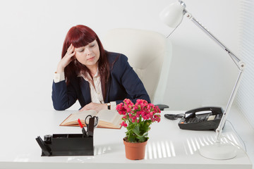 Confident business woman reads book in a office