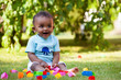 Little african american baby boy playing in the grass - 42110124