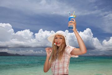 ビーチでパフェを食べる笑顔の女性