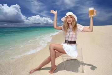 波打ち際でビールを持っている笑顔の女性