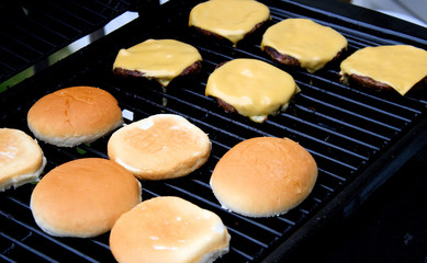 Cheeseburgers cooking on barbeque - buns toasting on side