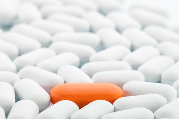 Individuality: Orange pill between white ones