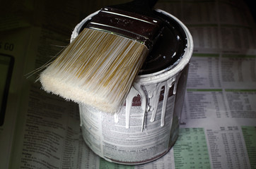 Messy Paint Can and Brush on Newspaper