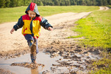 Boy splashing in puddle