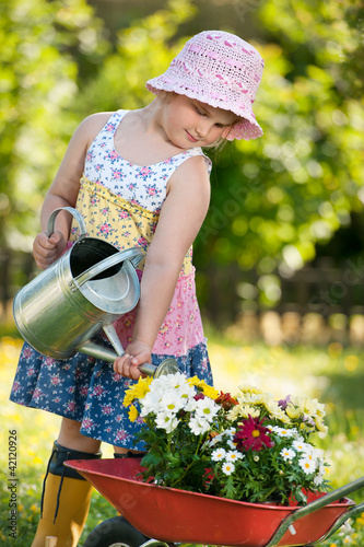 Little girl pouring flowers in the garden