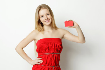 Young smiling woman holding blank credit card
