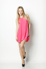 Full length of blond female in pink dress posing