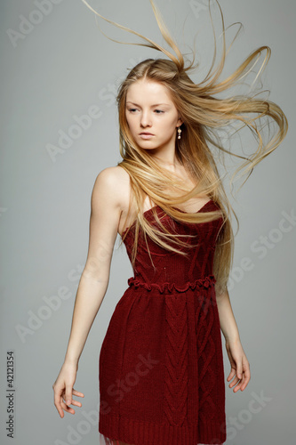 Blond fashion model posing with hair fluttering in the wind