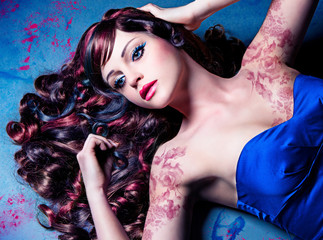 closeup of model with beautiful curly colored hair / haircolors
