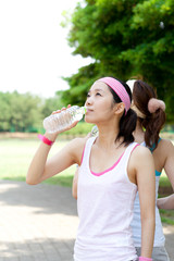 Beautiful young women drinking water at workout