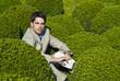 Mann sitzt in Büschen