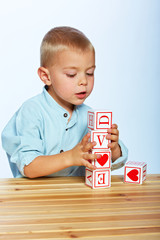 boy playing with alphabet blocks