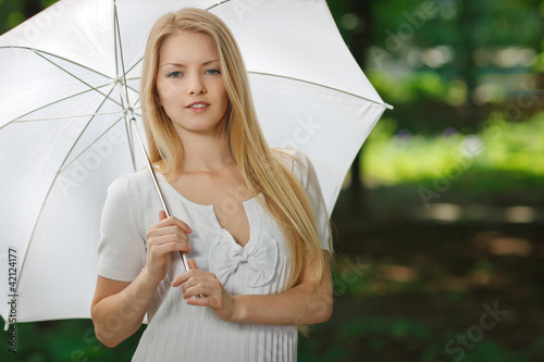 Young female standing outdoors under umbrella