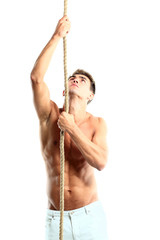Young male trying to climbing rope and looking up
